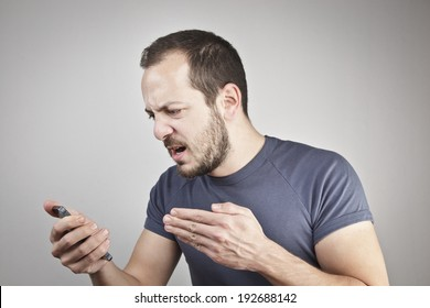 angry young man while answering smart phone not understood
