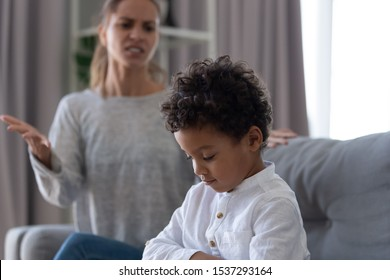 Angry young mother argue dispute with little biracial son behaving ill being stubborn, offended small boy child ignore avoid mad mother screaming talking to him. Parent child conflict concept