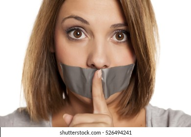 angry young woman with adhesive tape over her mouth, and finger in front of the tape