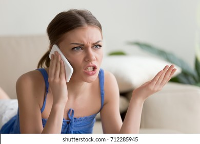 Angry young woman arguing talking on phone at home, dissatisfied girl calling customer service, having problem of conflict during telephone conversation, shouting gesturing while speaking by cell