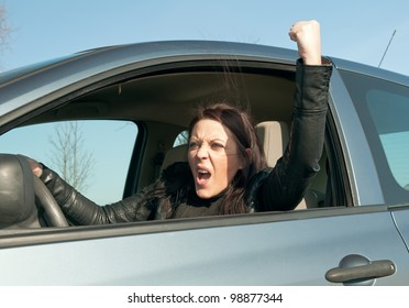 angry young woman in the car shows the fist