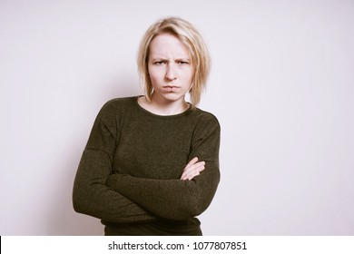 angry young woman frowning with arms crossed, negative emotion concept with copy space