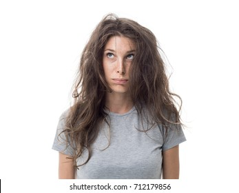 Angry young woman having a bad hair day, her long hair is messy and tangled
