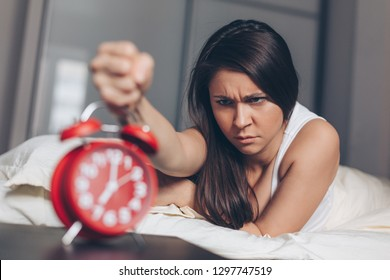 Angry young woman kill off alarm clock by fist on the bed in the morning. Awakening of the sleeping woman. Focus on woman.