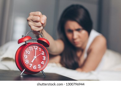 Angry young woman kill off alarm clock by fist on the bed in the morning. Awakening of the sleeping woman.