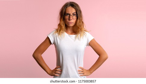 Angry young woman on pink background