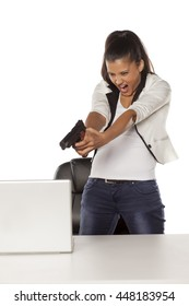 angry young woman is pointing a gun at her laptop
