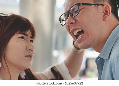 Angry young woman pulling ear lobe of surprised shocked in pain hurting funny man,cute girl showing pulls ear