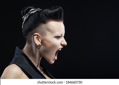 angry young woman screaming isolated on black background with copyspace