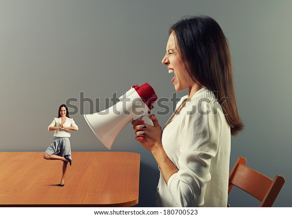 angry young woman screaming at small smiley woman in yoga pose