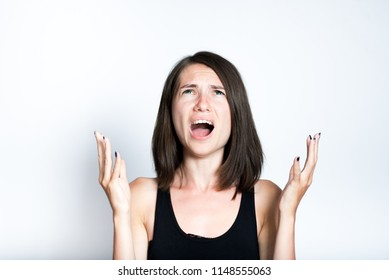 angry young woman screams with hysterics, isolated studio photo on gray background