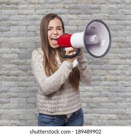 Angry young woman shouting with a megaphone
