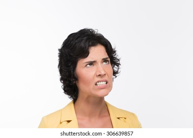 Angry young woman showing her teeth from annoyance. Black-haired woman in yellow jacket posing for photographer in studio.
