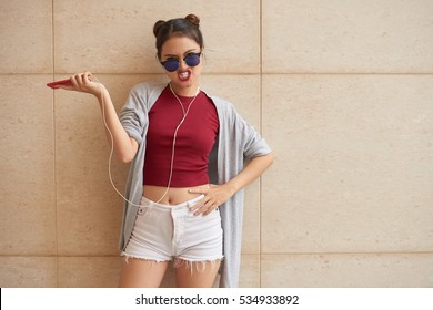 Angry young woman in sunglasses standing at the wall
