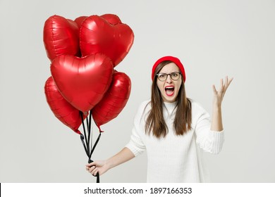 Angry young woman in sweater red hat glasses spreading hands screaming swearing celebrating birthday holiday party hold bunch of heart air inflated helium balloons isolated on white background studio