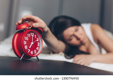 Angry young woman switches off the alarm clock on the bed in the morning. Awakening of the sleeping woman. Focus on alarm clock.