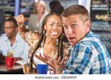 Angry young woman threatening rude man in cafe
