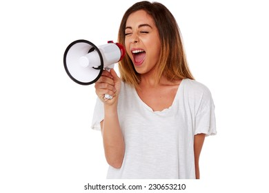 Angry young woman yelling into a handheld megaphone or bullhorn conceptual of a protest, rally, demonstration, leadership of public speaking, isolated on white