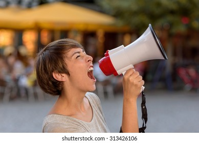 Angry young woman yelling into a megaphone as she stands on an urban street venting her frustrations during an open-air rally