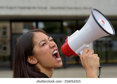 Angry young woman yelling over a megaphone or bullhorn as she participates in a street demonstration or protest airing her grievances, close up side view of her face