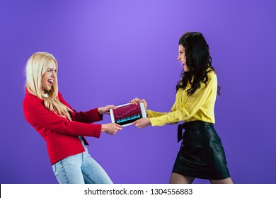 Angry young women fighting for digital tablet with traiding app on screen on purple background