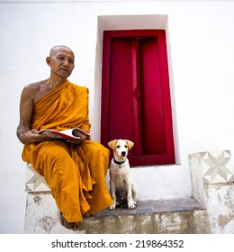 ANGTHONG, THAILAND - SEPTEMBER 24 : The Thai Buddhist monk relaxing with his dog sitting by, on September 24, at Angthong province, Thailand.