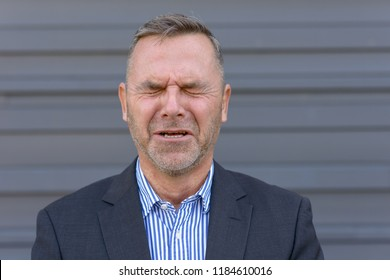 Anguished emotional businessman screwing up is eyes in a close up head and shoulders portrait against a grey wall with copy space