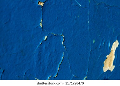 Angular fissures on a blue wall. Cracked plaster. Shabby painting of the walls. The blue putty falls off from the old white wall. The style of the cheek is chic. Waxing the walls. Selective focus.