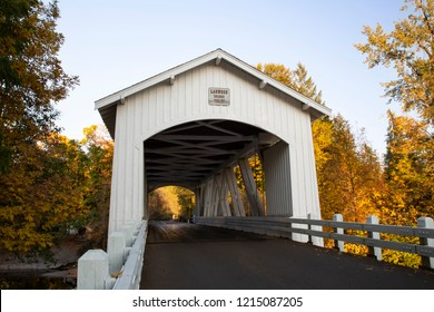 Angular perspective of Larwood covered bridge with fall color trees in a rural area in Oregon