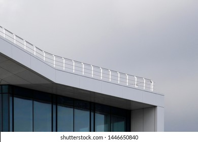 Angular terrace roof with steel balustrade. Close-up fragment of modern building with structural glazing under cloudy sky. Minimal business architecture photo with polygons and background for text.