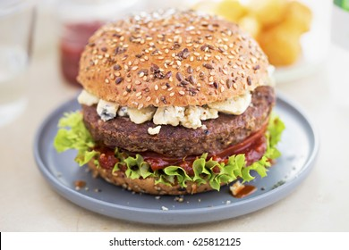 Angus burger on grain bun with tomato relish, lettuce and blue cheese