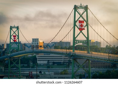 The Angus L MacDonald Bridge at dusk on Canada Day with large Canadian flags flying.