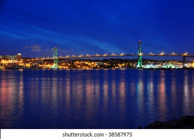 Angus L. Macdonald Bridge that connects Halifax to Dartmouth, Nova Scotia.  Taken at night with reflections in water