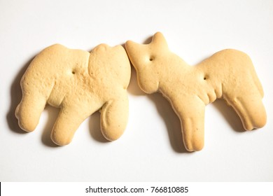 Animal cracker shot close up against a white background, elephant and donkey, republican and democrat, political politics clash headbutt
