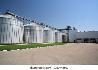 Animal feed factory. Big modern granary in sunny summer day. Metal containers for grain