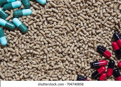 Animal feed pellets and pill capsules as background, antibiotics in livestock feed concept.