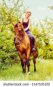 Animal, horsemanship concept. Young woman sitting and ridding on a horse through garden on sunny spring day
