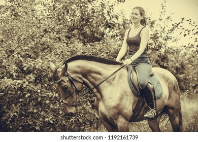 Animal, horsemanship concept. Young woman sitting and ridding on a horse through garden on sunny spring day, sepia