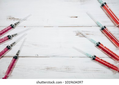 Animal injections. White board background with syringe, close up, top view. Pet care and veterinary concept. Space for your text or image.