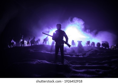 Animal protection or Hunting concept. Silhouette of a man (hunter) with rifle standing against group of animals in colorful dark backlight. Decorated with miniatures. Selective focus