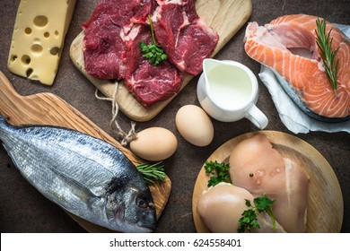 Animal protein food at stone table. Meat, chicken, fish, egg, beans, milk.