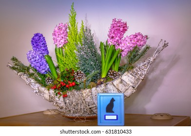 Animal urn for a dead cat ashes with flowers in a floreal plant composition. Copy space blank label for animal name, isolated blurred background. Concept of animal death and sorrow for affective loss.