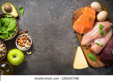 Animal and vegan Protein sources. Meat, fish, eggs, cheese,  nuts, greens, oil, fruit. Top view on dark stone table.