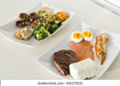 Tier gegen Pflanzenproteine: ein Teller mit Rind-, Eier-, Lachs-, Käse- und Hühnergrill und ein anderer mit Nüssen, Pilzen, Broccoli, Lentil, Hummus und Quinoa