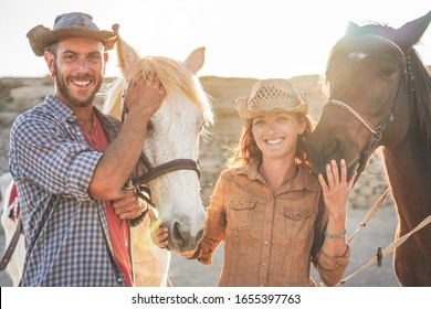 Animals lovers couple taking with bitless horses during sunny day inside ranch corral - Happy people having fun training at their farm - Love and wild concept - Focus on guys faces
