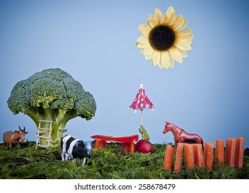 Animals on creative farm or garden made of vegetables: broccoli tree, dill grass, red pepper bench, carrot fence and sunflower sun, concept.