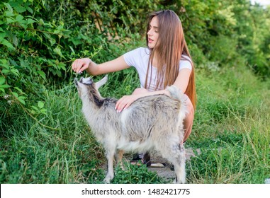 Animals are our friends. happy girl love goat. village weekend. summer day. Love and protect animals. contact zoo. veterinarian lamb goat. woman vet feeding goat. farm and farming concept.