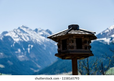 Animals' wooden house on blurred mountains background, animals care, Alps landscape