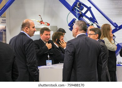An animated conversation of people at the counter. St. Petersburg, Russia - 3 October, 2017. Participants and visitors of the annual St. Petersburg Gas Forum.