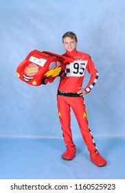 Animator in the costume of Lightning McQueen on a blue background
